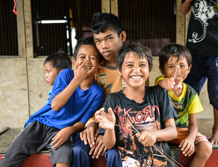 developing country: Semporna, Malaysia - Oct 2, 2014    A group of poor little Bajau boys having funs in front of camera on street, shot on Mabul island, Semporna, Sabah, Maylaysia  Bajau people are also referenced as the last sea gypsies,  sea-oriented, boat-dwelling, nomad