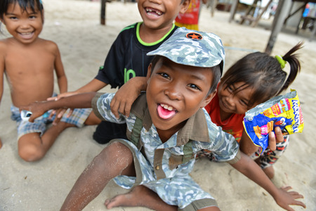 Semporna, Malaysia - Oct 2, 2014    A group of poor little Bajau boys and girls having funs in front of camera on street, shot on Mabul island, Semporna, Sabah, Maylaysia  Bajau people are also referenced as the last sea gypsies,  sea-oriented, boat-dwell