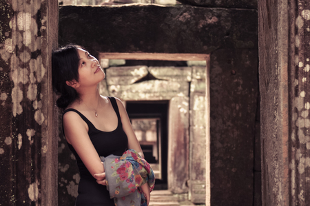 doorframe: single young woman leans on pillars of ancient doorframe, smiling, looking aside,  Angkor Wat, Camobdia