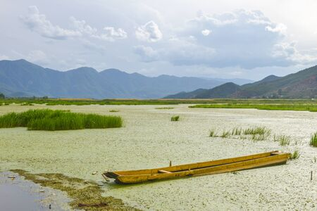 Single boat on Lugu Lake surrounded by mountains under cloudy sky, in Lijiang, Yunnan, China Stock Photo