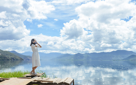 Single young Chinese woman in white long skirt stands by Lugu lake Stok Fotoğraf - 108566929