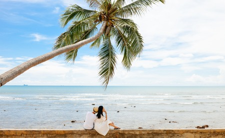 young Asian couple leans on each other under one palm tree at tropical beach, Lanta island, Krabi, Thailand. Stock Photo