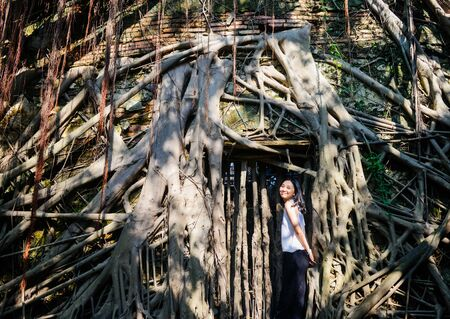 Single young Asian girl smile to camera standing before the famous old tree house at Anping, Taiwan