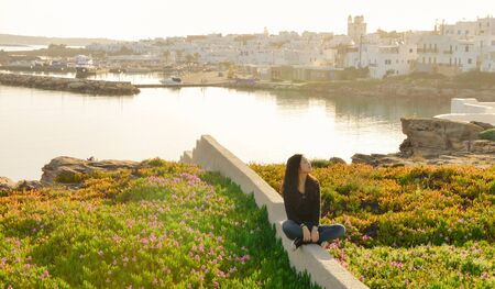 Single Asian girl sits among blossomed flowers when sunrise in Spring season on Paros island, Greece