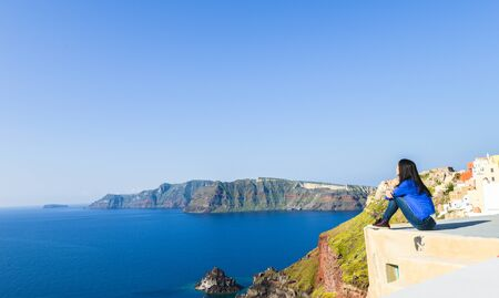 Single Asian girl sitting on edge of roof top and looking at horizon at Oia town, Santorini, Greece