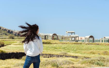 beautiful young woman turns her face around with her long black hair flying in the wind