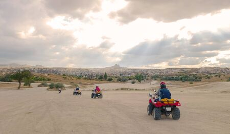 Group of young people ridding ATVs in Goreme National Park just before sunset at Cappadocia, Turkey