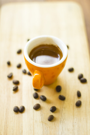 coffee cup and coffee beans on wood  selective focus with shallow depth of field