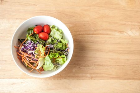 mixed Salad bowl on wooden table close up top view