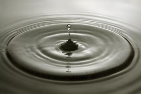 Gouttelettes d'eau et concentriques ondulations sur une surface grise.