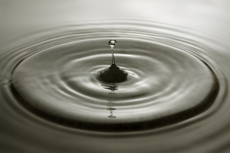 Water droplet and concentric ripples on a grey surface. Stock Photo