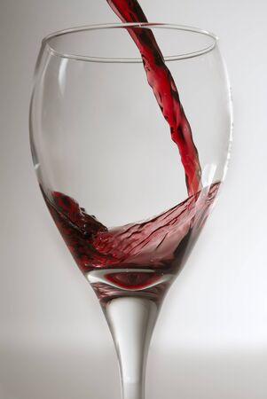 Vin rouge �tant vers� dans un verre de vin propre contre un backround gris. Banque d'images