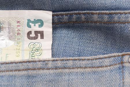 sterlina: Fotografia Macro di 5 sterline in una tasca dei jeans.