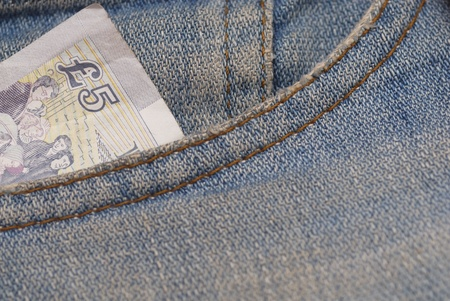Macro photograph of £5 sterling in a Jeans pocket.
