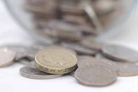 libra esterlina: Monedas derramado en tarro de cristal, se centran en una moneda. Sterling. Foto de archivo