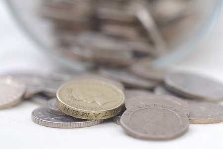 pound coin: Spilled Coins from Glass Jar, focus on £1 coin. Sterling. Stock Photo