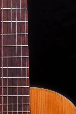 fretboard: Detail of classic guitar fretboard (Spanish), against black background.