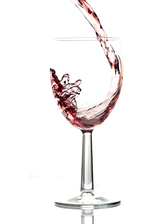 Red wine pouring into wine glass. White background, reflexion. photo