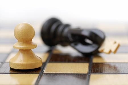 conflictos sociales: Pe�n blanco de pie sobre el rey derrotado negro. Lucha de clases.