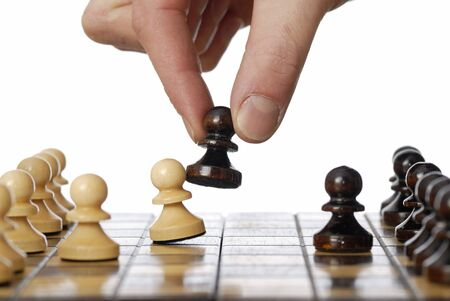 Hand moving black chess piece taking a white pawn. photo