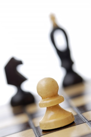 Tilted view of chessboard, focus on pawn in foreground.