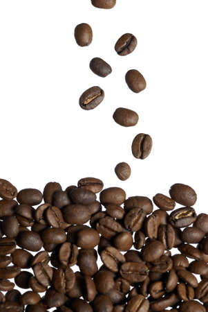 Arabica coffee beans falling into stack. Focus on falling beans. photo