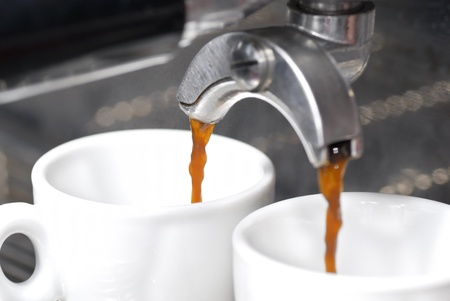 A shot of coffee pouring into two espresso cups. Focus on rear portafilter spout.