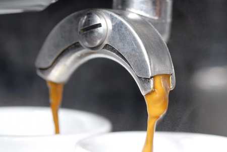 A shot of coffee pouring into two espresso cups. Focus on near portafilter spout. Stock Photo