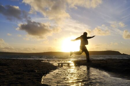 Silhouette of one man jumping over water at the beach. Stock Photo - 13677729