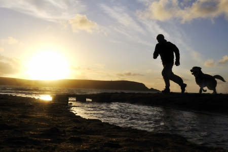 Silhouette of one man running on the beach with his dog.