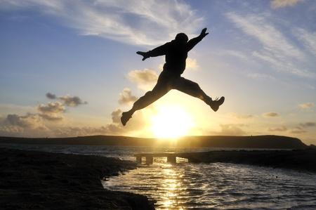 Silhouette d'un homme sautant par-dessus l'eau � la plage. Banque d'images