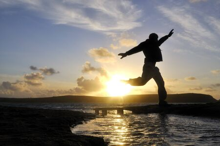 Silhouette of one man jumping over water at the beach. Stock Photo - 13677732
