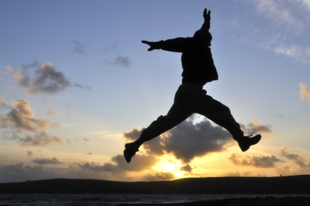 Silhouette of one man jumping over water at the beach.