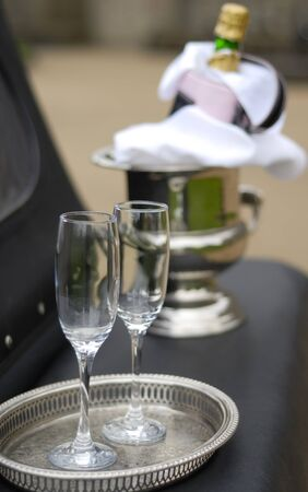 Two Champagne glasses and bottle on ice at wedding.