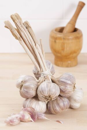 Bunch of tied garlic on wooden kitchen work surface.