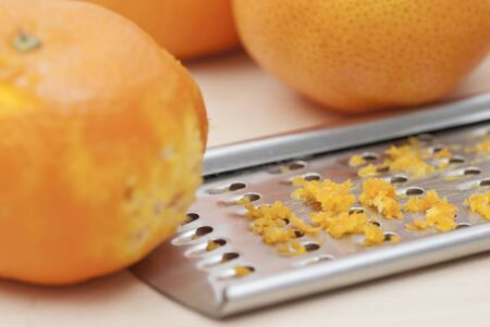 Grater and citrus zest on wooden kitchen surface. Stock Photo - 16724829