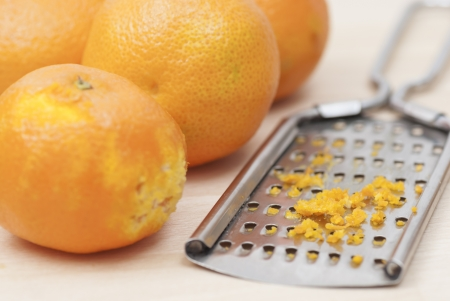 Grater and citrus zest on wooden kitchen surface. Stock Photo - 16724855