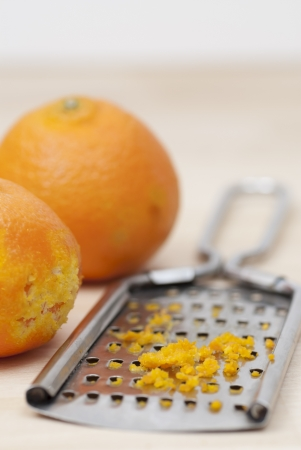 Grater and citrus zest on wooden kitchen surface. Stock Photo - 16724845