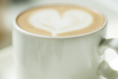 latte art: Small coffee cup with heart design in milk.