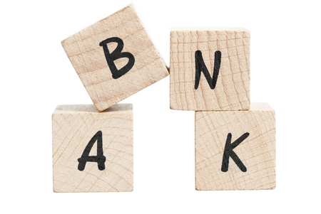 Bank spelled out with wooden blocks  White background  Stock Photo - 18004452