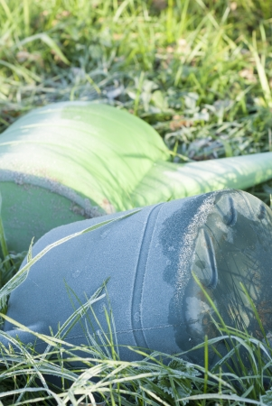 Two watering cans covered in frost on allotment.