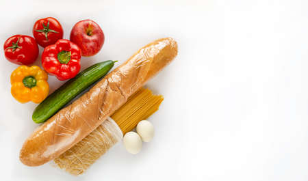 A grocery set is on a white background. The set includes pasta, bread, vegetables. Products are intended to be donated during the coronovirus epidemic.