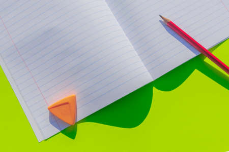 Concept for background on September 1. Children go to school again. An open notebook, office supplies are located on a colored background. There is a place for the text
