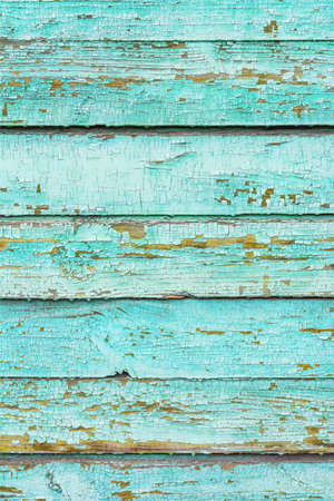 The surface of an old light green, cracked wood plank as a texture. The boards are laid horizontally. Vertical image.