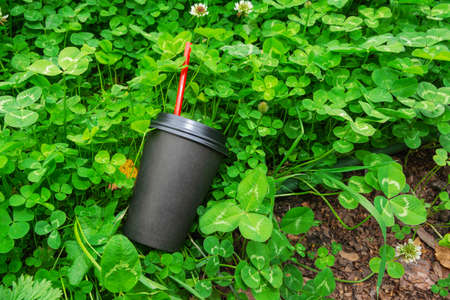 A black paper cup for coffee with a red straw lies in the grass. Environmental pollution with household waste. Imagens