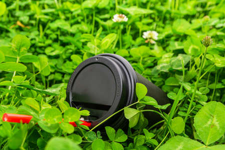 A black paper coffee cup with a red straw is thrown into the green grass. Environmental pollution with household waste.