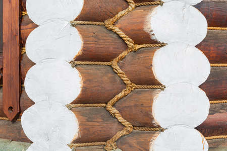 Fragment of the corner of a log house, decorated with a decorative rope. Wooden architecture.