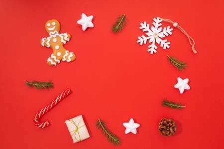 A Christmas composition consisting of a gingerbread man, gifts, a Christmas tree, a snowflake and a lollipop is located on a red background. New Year and Christmas concept. There is a place for text.
