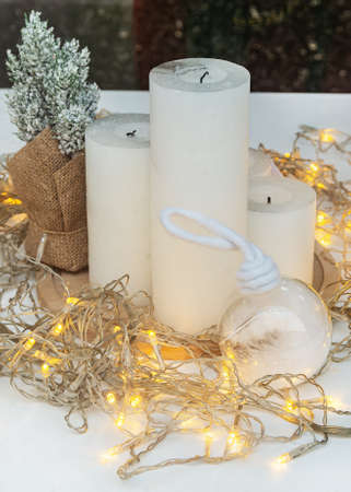 New Year's composition, consisting of white candles and glowing bulbs. New Year and Christmas concept.