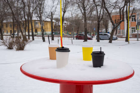 Four cups of coffee are on a snow-covered table in a winter park.